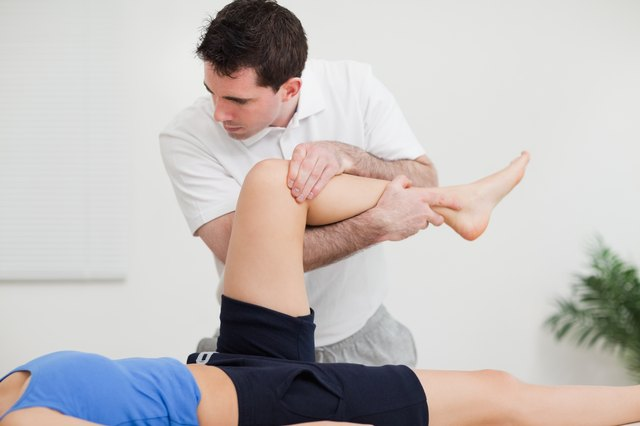 Chiropractor holding the leg of woman while standing