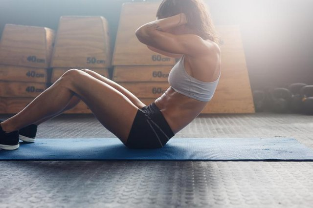 Indoor shot of fitness female working out at the gym. Muscular young woman doing stomach exercises.