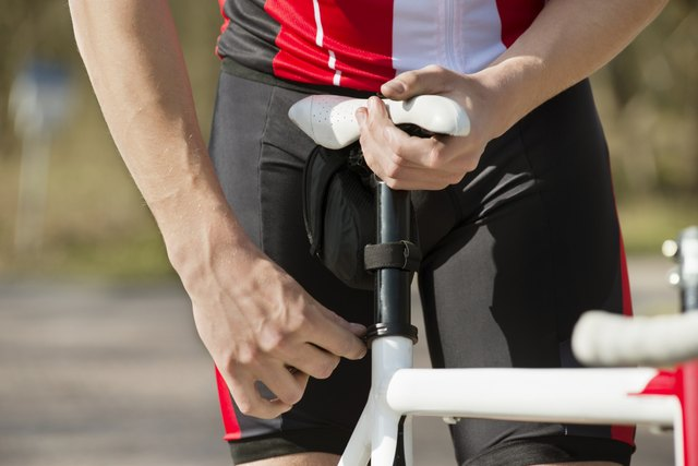 Man Adjusting Seat Of Bicycle