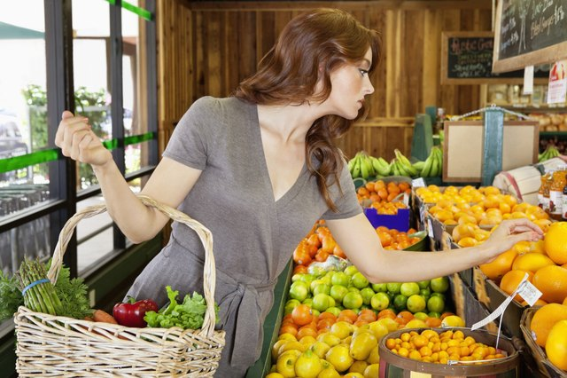Beautiful young female shopping for fruits in market