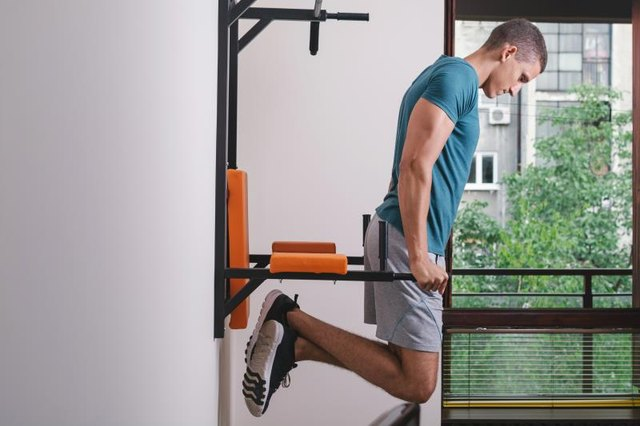 Muscular man working out in front of window
