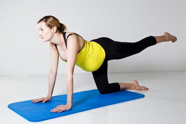 Pregnant woman exercising on mat