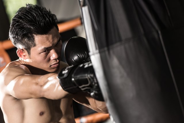 young muscular fighter training on a punching bag