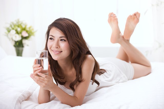 Young lady drinking on bed