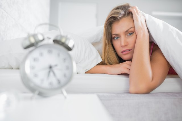 Exhausted blonde looking at camera with alarm clock in foreground