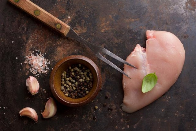 Raw chicken breast with rosemary, garlic and peppercorns, selective focus. Culinary cooking ingredients