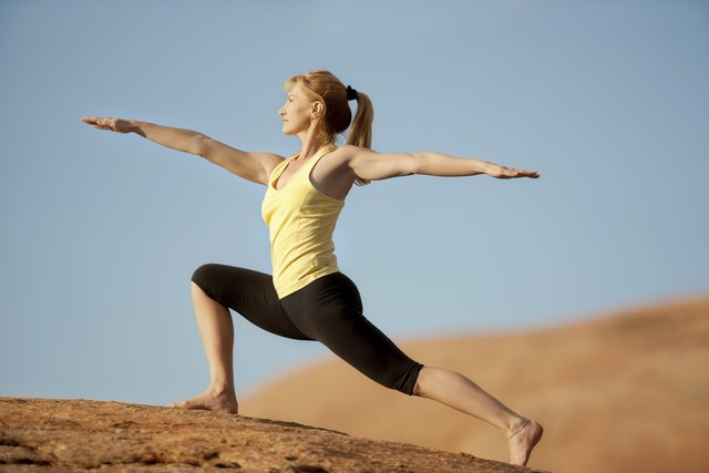Woman Outside Against Blue Sky In Warrior 2 Yoga Position