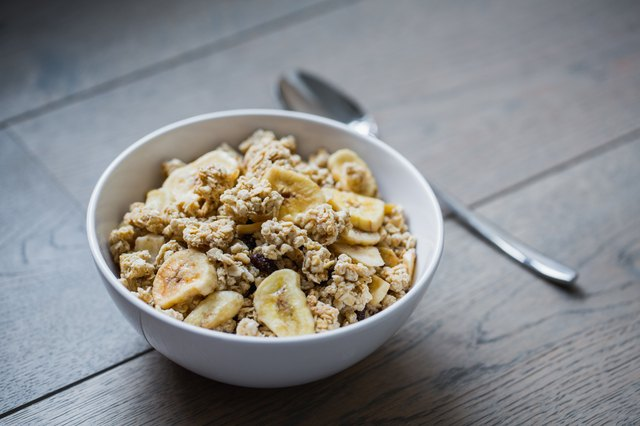Bowl of granola with banana slices with milk on table.
