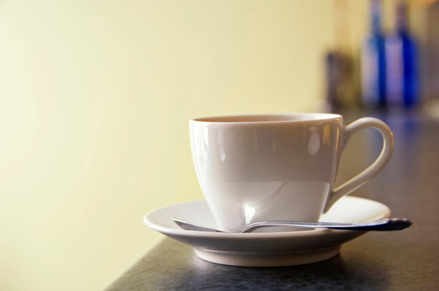 Cup and saucer of coffee on European cafe counter.