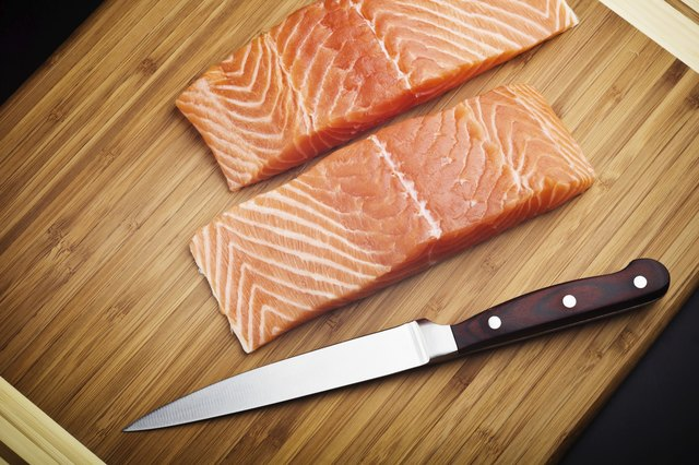 salmon fillet with knife on wood board