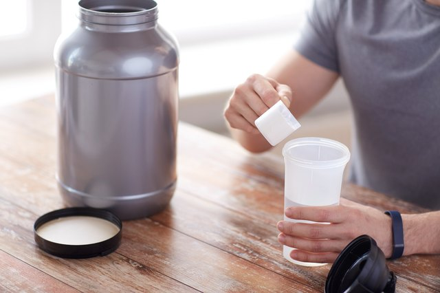 Man pours protein powder into a cup.