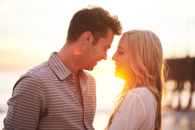 Couple smiling at each other on the beach.