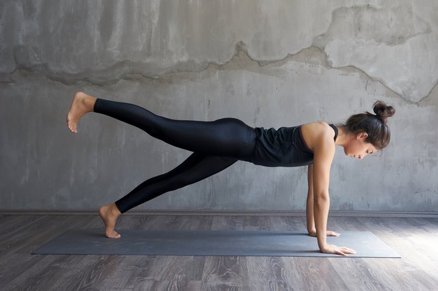 woman doing one-leg plank pose yoga