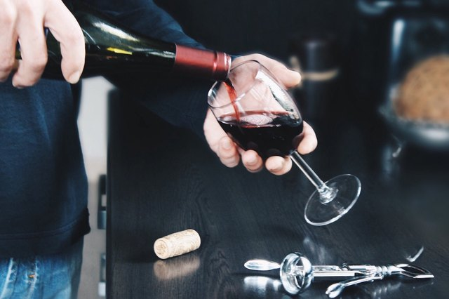 A man pours a glass of wine.