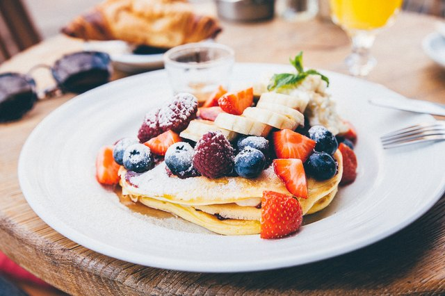 A stack of pancakes topped with fruit