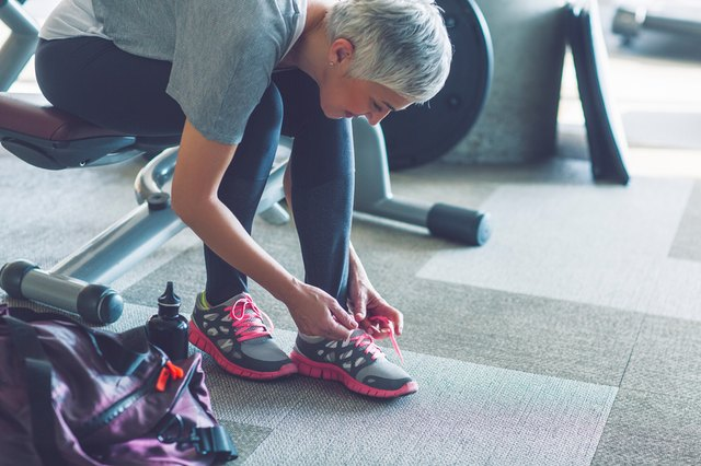 older woman at gym tying shoes