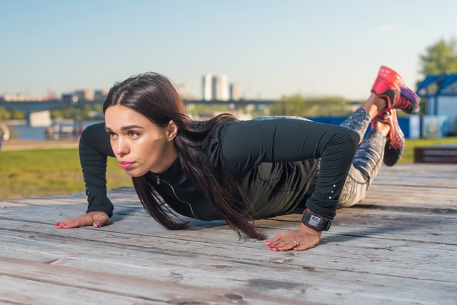 woman doing push-ups on her knees