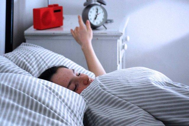 Woman turning off morning alarm.