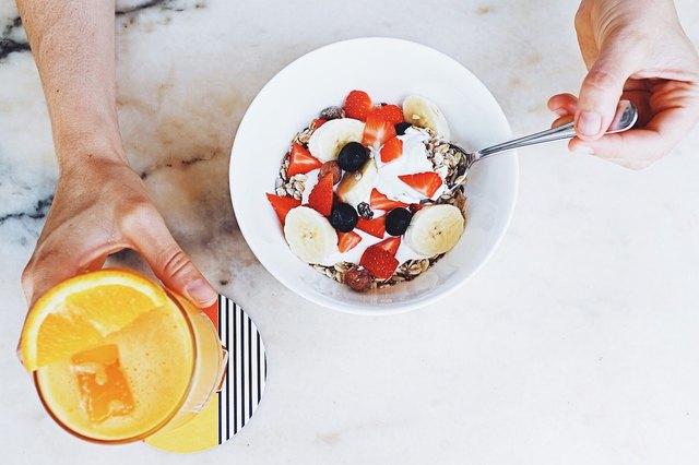 A man eats yogurt at breakfast.