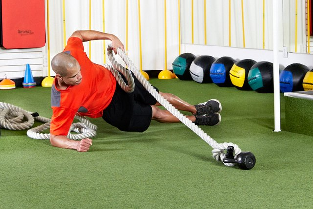 Man doing Side Plank With Rope Pull with the battle ropes
