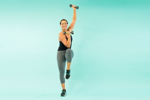 woman doing a weighted standing bicycle crunch