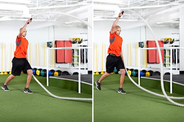 Man doing scissor jumps with alternating waves with the battle ropes
