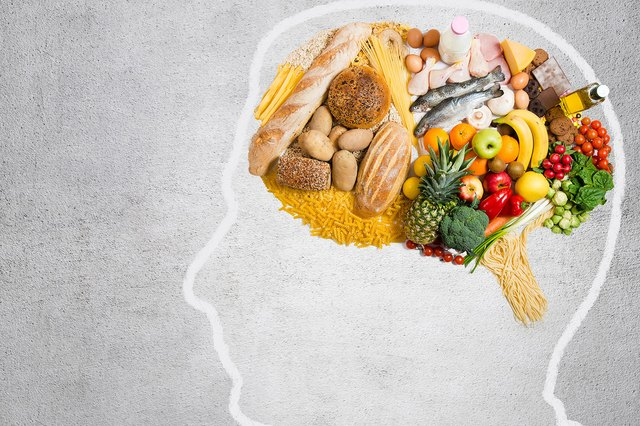 An outline of a person's head filled with healthy foods like fruit, vegetables and fish