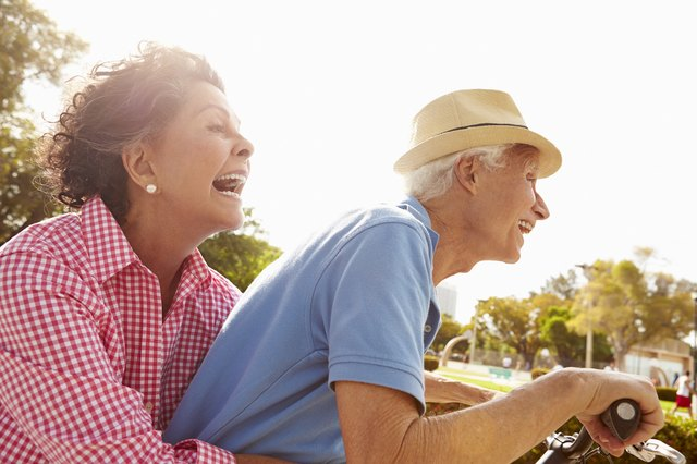 An elderly couple happily rides a bike.