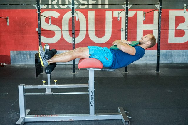 man doing a ghd weighted sit-up crossfit exercise