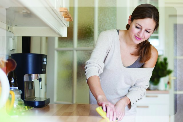 Woman cleaning counter with a sponge