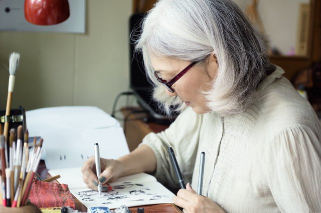 An elderly woman draws quietly at her desk.