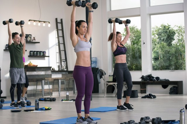 Autumn Calabrese leads her team in overhead dumbbell presses