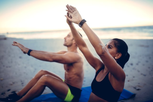 A couple stretches on the beach.