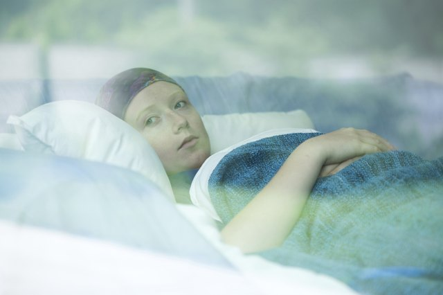Female cancer patient looks pensive as she reclines on a pillow.