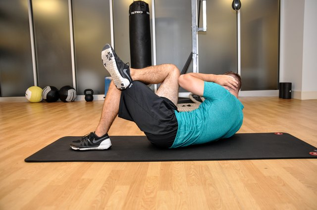 The ending position of the cross-body sit-up with the left elbow touching the right knee.