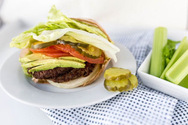 lettuce-wrapped burger with tomatoes and pickles