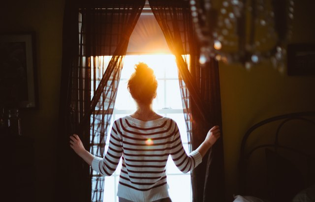 woman looking out window in morning