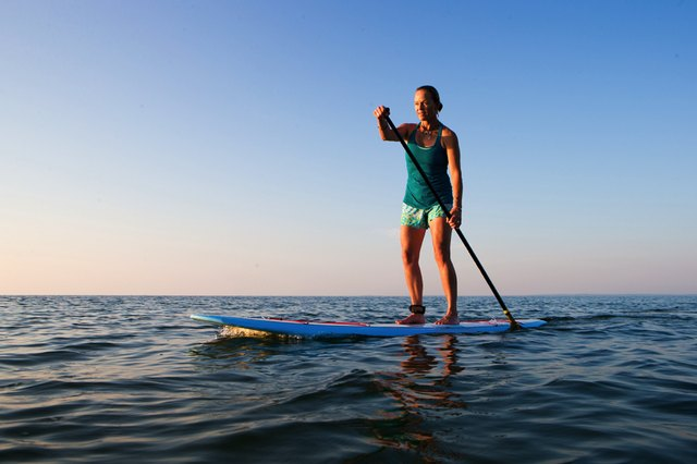 fit woman paddleboarding