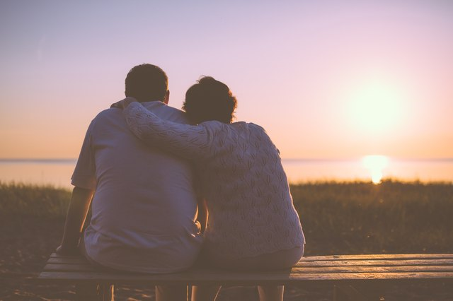 An elderly couple watches the sunset over the ocean.