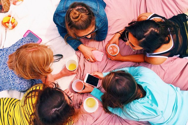Girls hanging out on a picnic blanket.