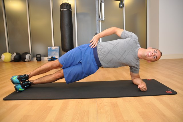 The hips high position of the side plank crunch. The model has his hips raised in this position, left arm planted under him, right hand on his hip, and feet stacked on top of each other.