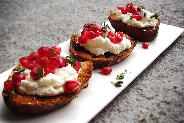 A white plate with three bruschetta topped with ricotta and pomegranate seeds