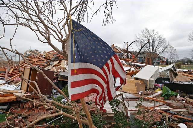 Tattered U.S. flag hangs from a tree in front of tornado devastation in Garland, Texas.