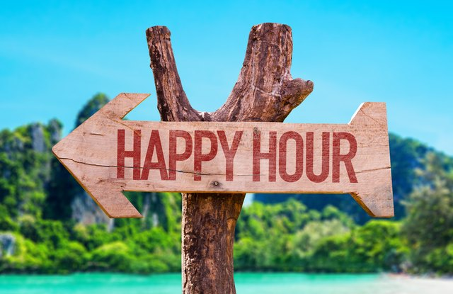 """Sign on the beach that reads """"Happy Hour""""."""