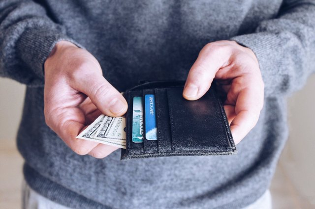 A man pulls money out of a wallet.