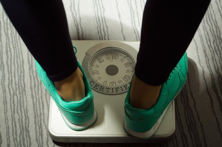 Female legs stand on scales