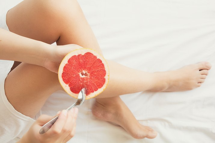 Healthy eating concept. Woman having grapefruit in bed. Top view. Toned