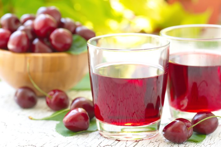 cherries and a glass of cherry juice on a wooden table