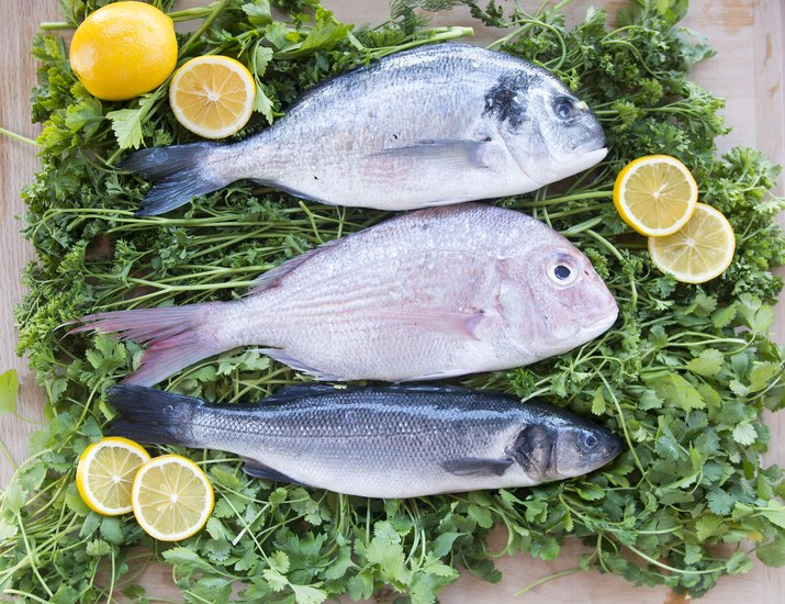 Raw fish on a bed of greens with lemons
