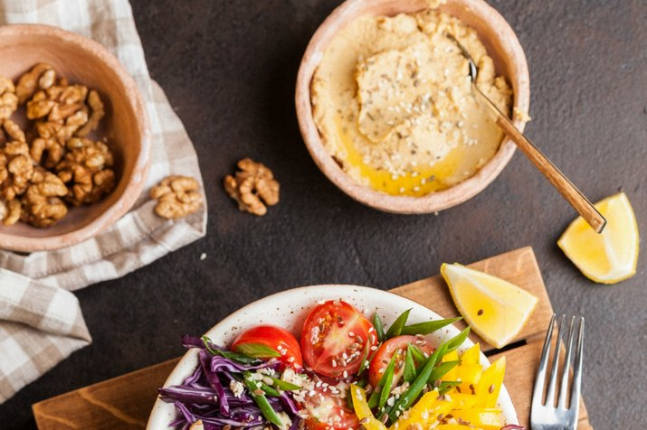 Hummus, tomatoes and walnuts on table